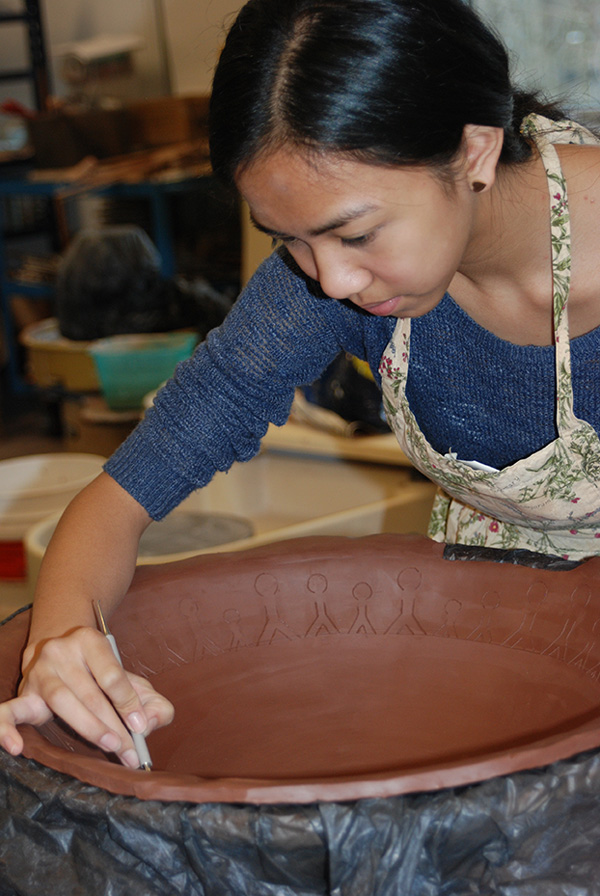 Student Carving Design into a clay bowl in Ceramics Class