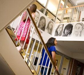 People Looking at Students Portrait Drawings on the Walls